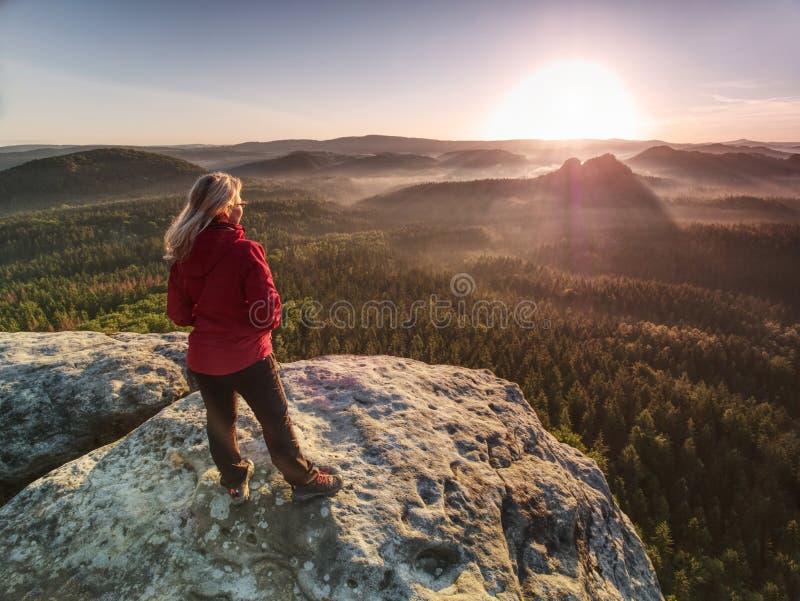 Женщина в на открытом воздухе одеждах наслаждается взглядом на саммите в горах стоковые фотографии rf