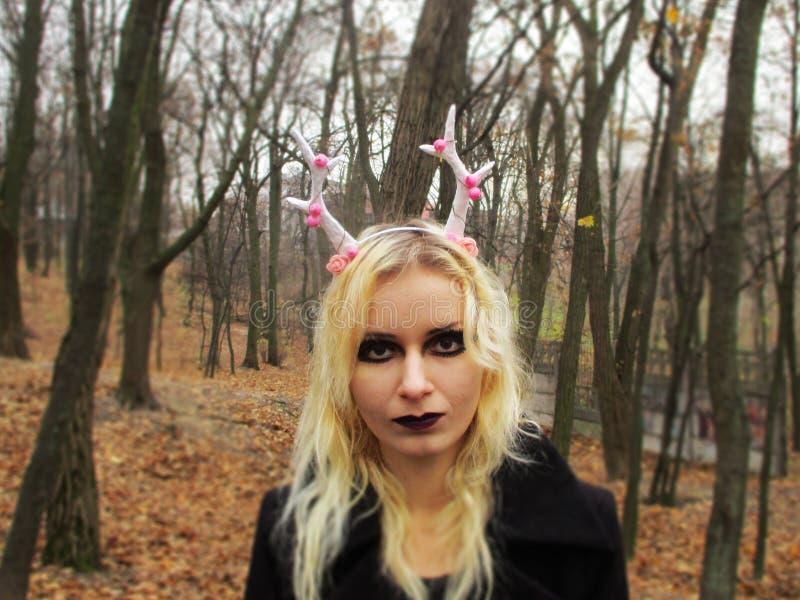 Женщина в новогодней копыт с оленьими рогами в лесу стоковые изображения