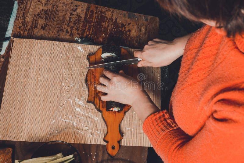 Женщина в отрезках кухни нож с креном суш на уровне частей для посетителей стоковые фото