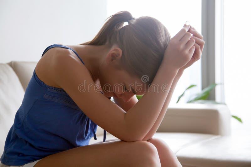 Женщина в отчаянии через развод сидя с кольцом стоковые изображения