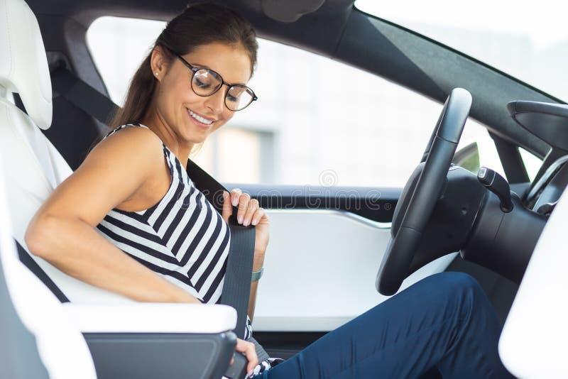 Женщина в очках сидит в машине и пристегивает ремень безопасности стоковые фото