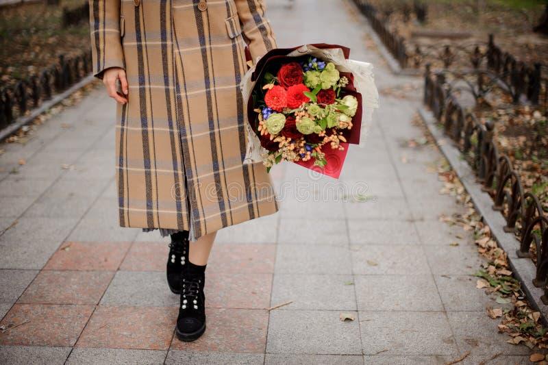 Женщина в пальто шотландки идя с букетом цветков на всех стоковые фотографии rf