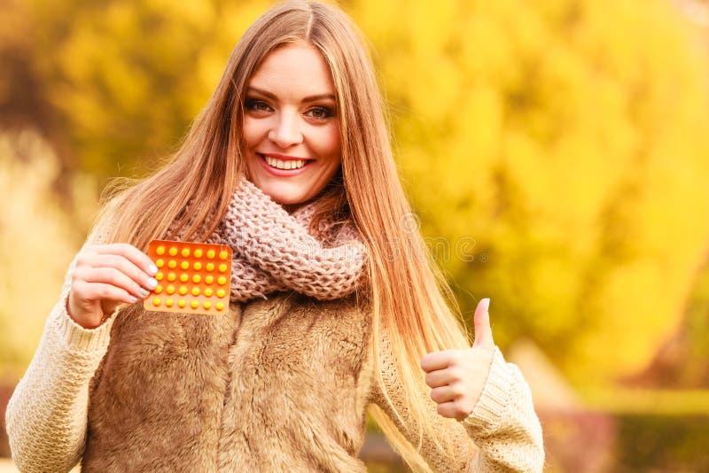 Женщина в парке осени держа медицины витаминов стоковые фотографии rf