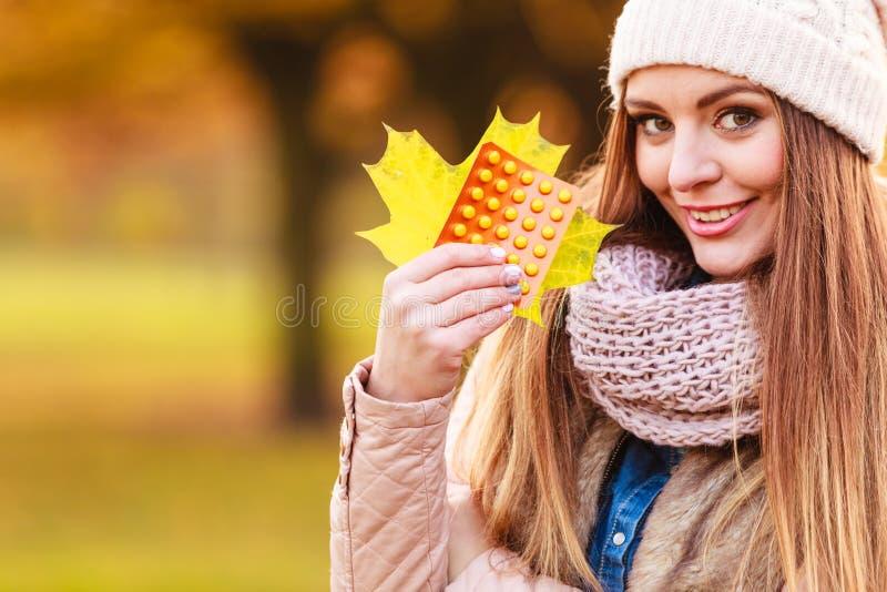 Женщина в парке осени держа медицины витаминов стоковое фото rf