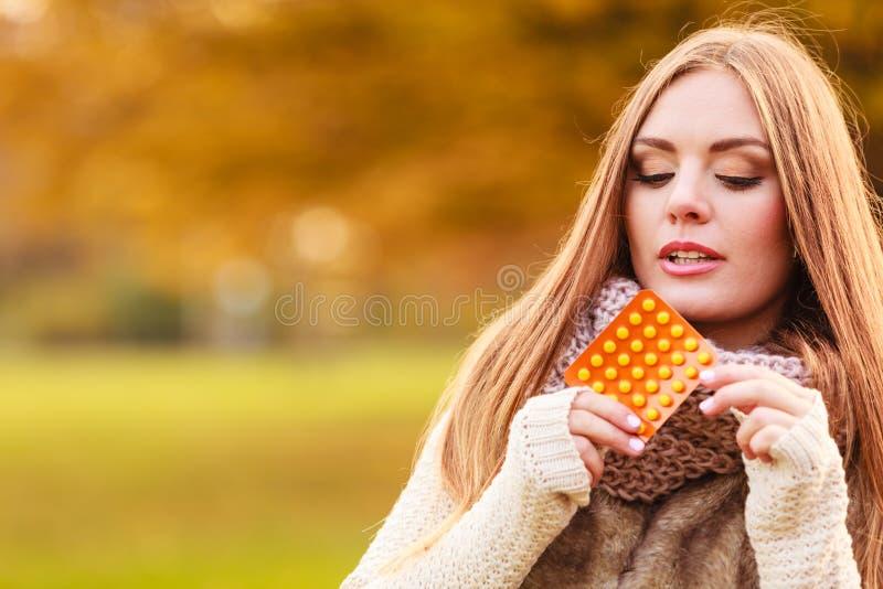 Женщина в парке осени держа медицины витаминов стоковое изображение rf