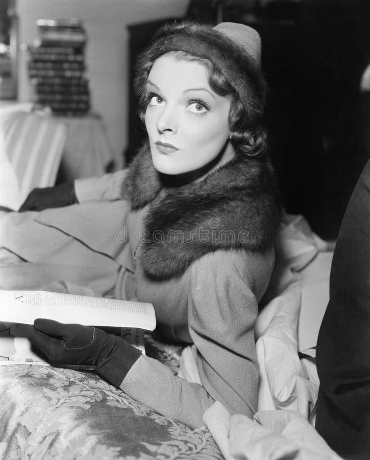 Женщина в пальто и шляпе читая кассету (все показанные люди более длинные живущие и никакое имущество не существует Th гарантий п стоковые фотографии rf