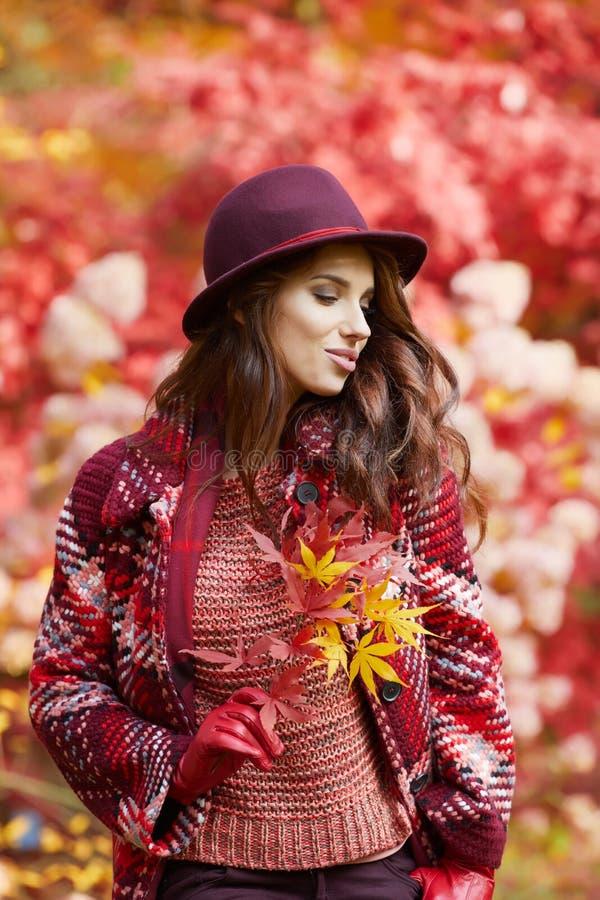 Женщина в пальто с шляпой и шарф в осени паркуют стоковая фотография rf
