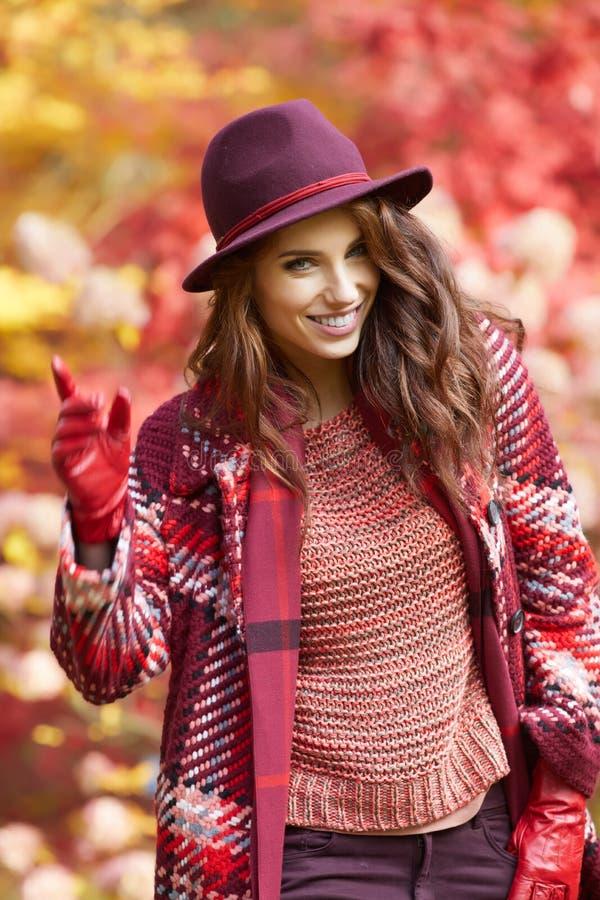Женщина в пальто с шляпой и шарф в осени паркуют стоковая фотография