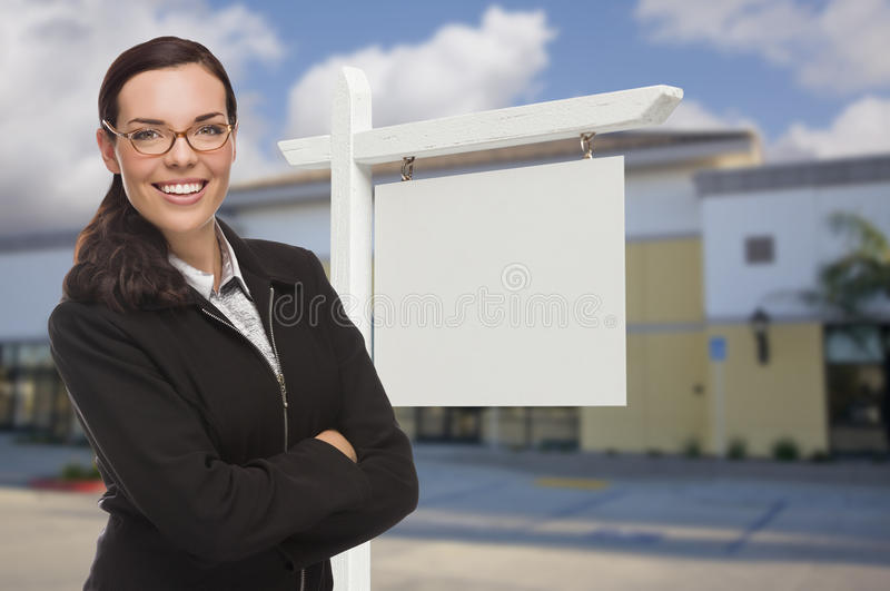 Женщина в переднем коммерчески здании и пустом знаке недвижимости стоковые изображения