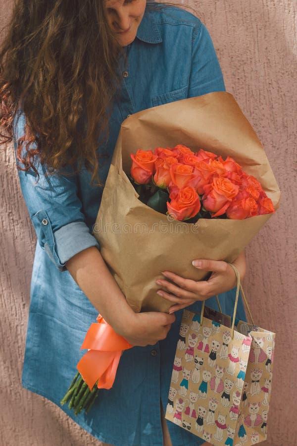 Женщина в платье джинсовой ткани с букетом роз и бумажного мешка подарка стоковое фото rf