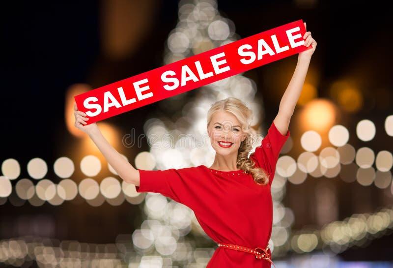 Женщина в платье с красным знаком продажи стоковое изображение rf