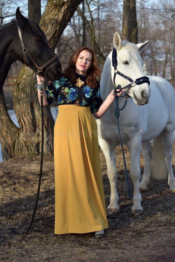 Женщина в платье с 2 лошадями весной стоковые изображения rf
