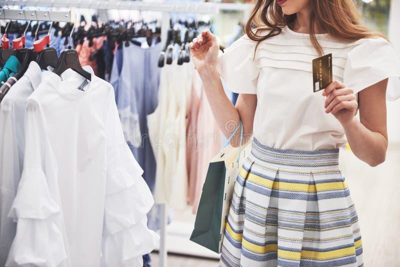 Женщина в покупке Счастливая женщина с хозяйственными сумками и кредитная карточка наслаждаясь в покупках Защита интересов потреб стоковые изображения