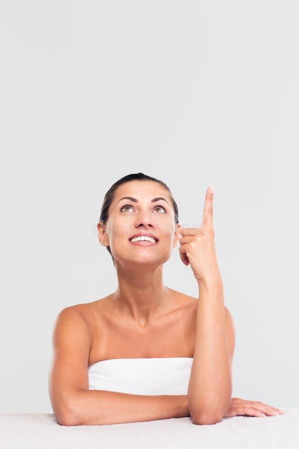 Женщина в полотенце сидя на таблице и указывая палец вверх стоковое фото rf