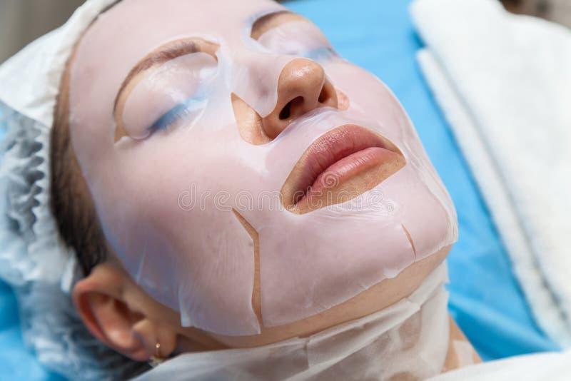 Женщина в процедуре по косметики маски стоковая фотография rf