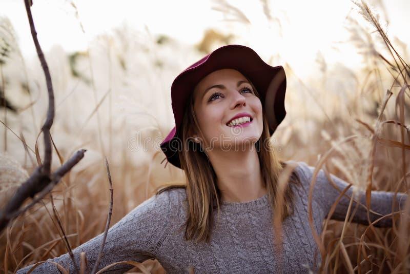 Женщина в пшеничном поле на заходе солнца стоковое изображение rf