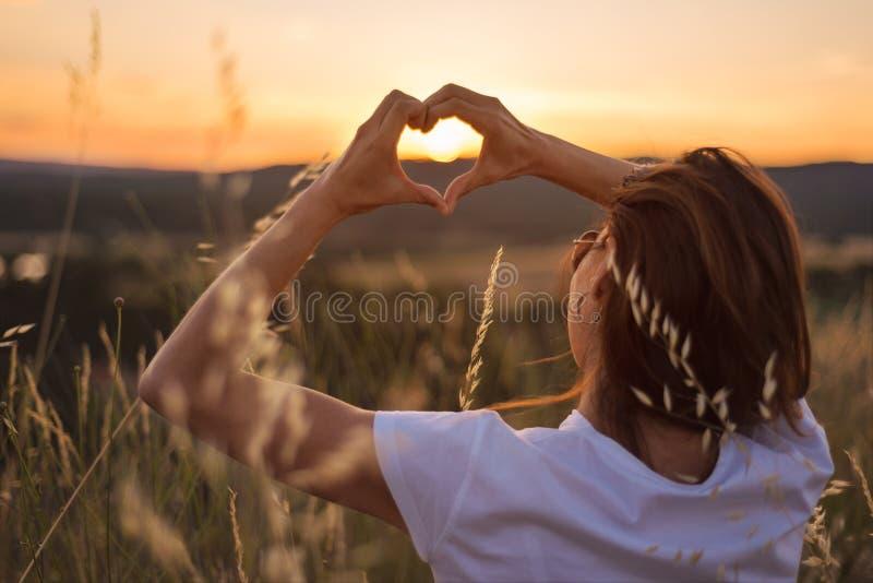 Женщина в пшеничном поле формируя форму сердца с руками на заходе солнца стоковые изображения rf