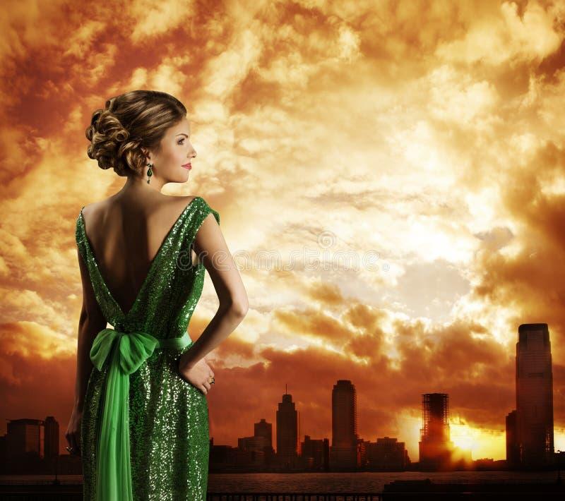 Женщина в платье, заходе солнца неба города, вид сзади фотомодели стоковые фото