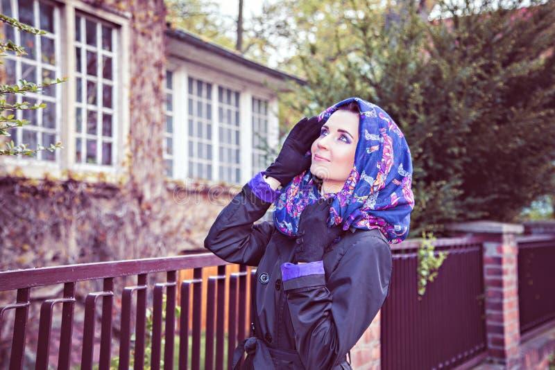 Женщина в плаще и шарфе на фронте головы загородки стоковые фото