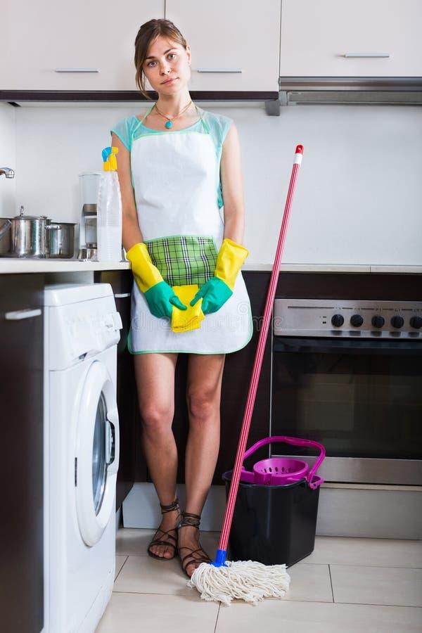Женщина в резиновых перчатках на кухне стоковое фото rf