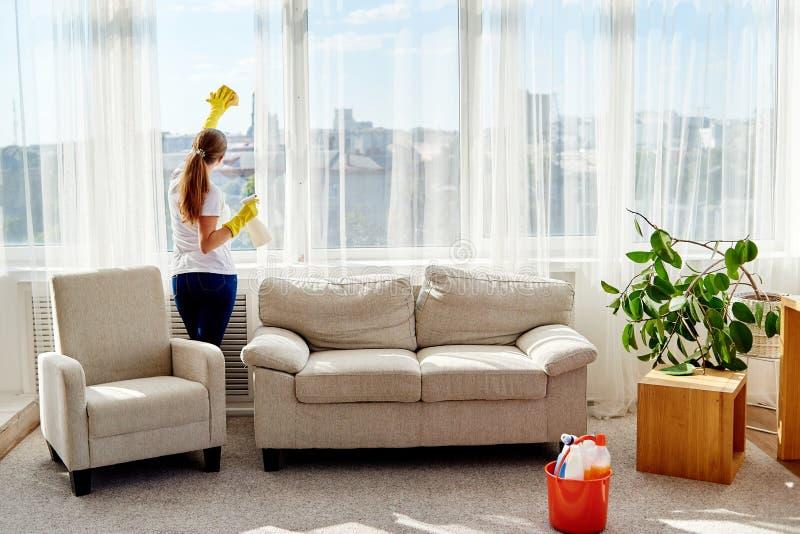 Женщина в резиновых перчатках очищая окно с брызгами и бульварной газетенкой cleanser дома, космос экземпляра, взгляд задней част стоковое фото rf