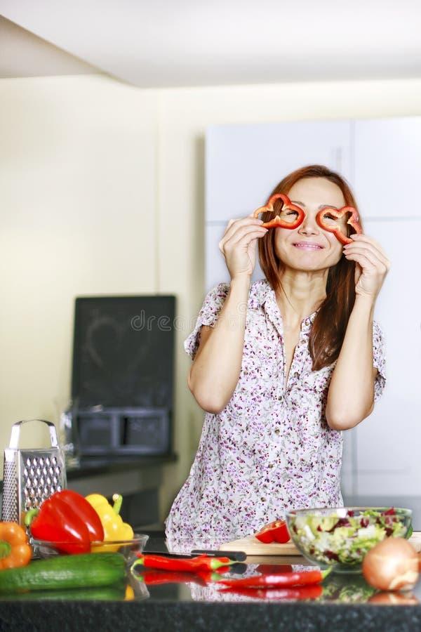 Женщина в рисберме покрывая ее глаза с перцем и усмехаясь в кухне стоковая фотография