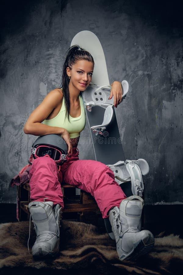 Женщина в розовом костюме snowboarder держа сноуборд стоковые фотографии rf