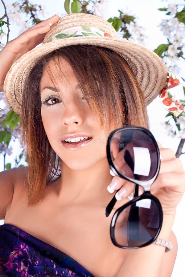 Женщина в розовых платье, шлеме и солнечных очках лета стоковое изображение
