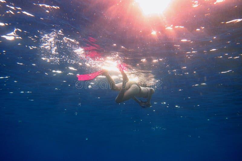 женщина в розовых ребрах в голубом море стоковое изображение