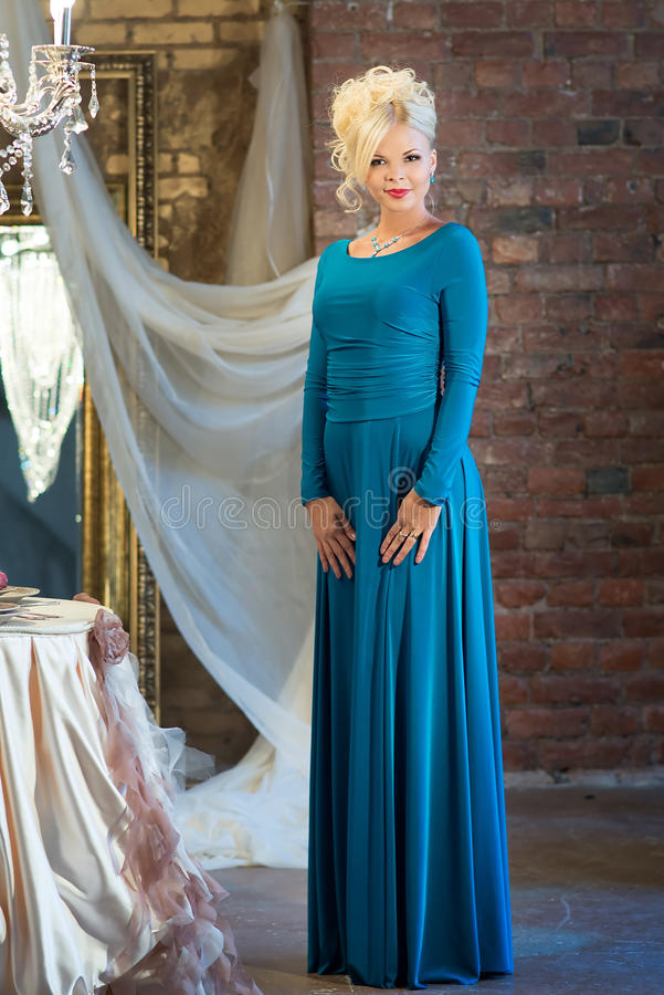 Женщина в роскошном интерьере blocky голубое maike платья стоковое изображение