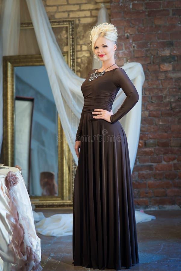 Женщина в роскошном интерьере blocky Платье Брайна стоковые фото