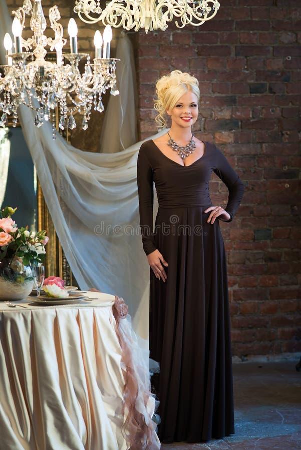 Женщина в роскошном интерьере blocky Платье Брайна стоковые изображения