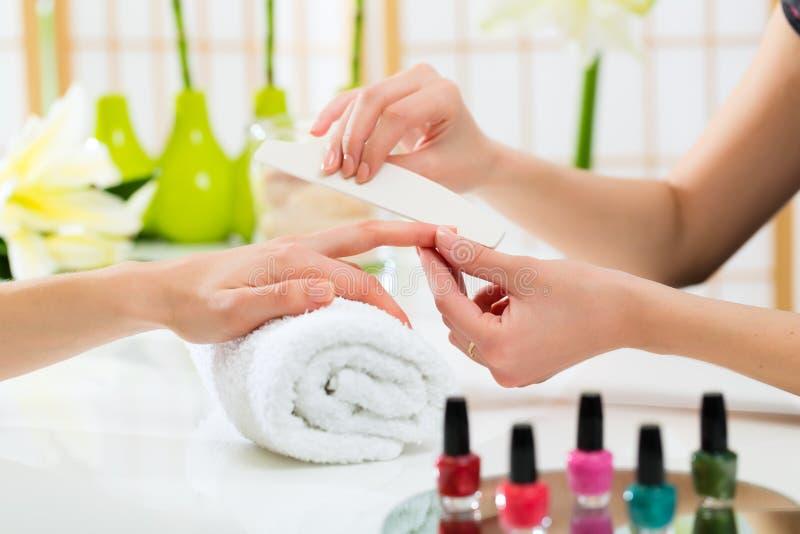 Женщина в салоне ногтя получая маникюр стоковая фотография rf