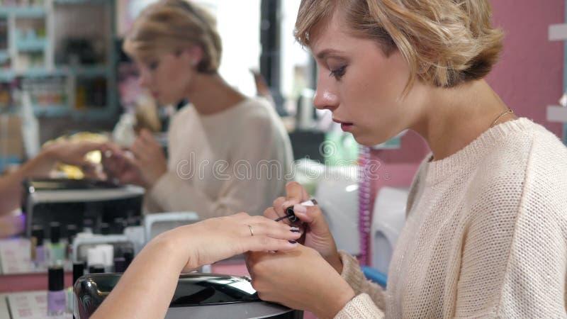 Женщина в салоне ногтя получая маникюр beautician с файлом получать ногти к клиенту запачканный стоковое фото