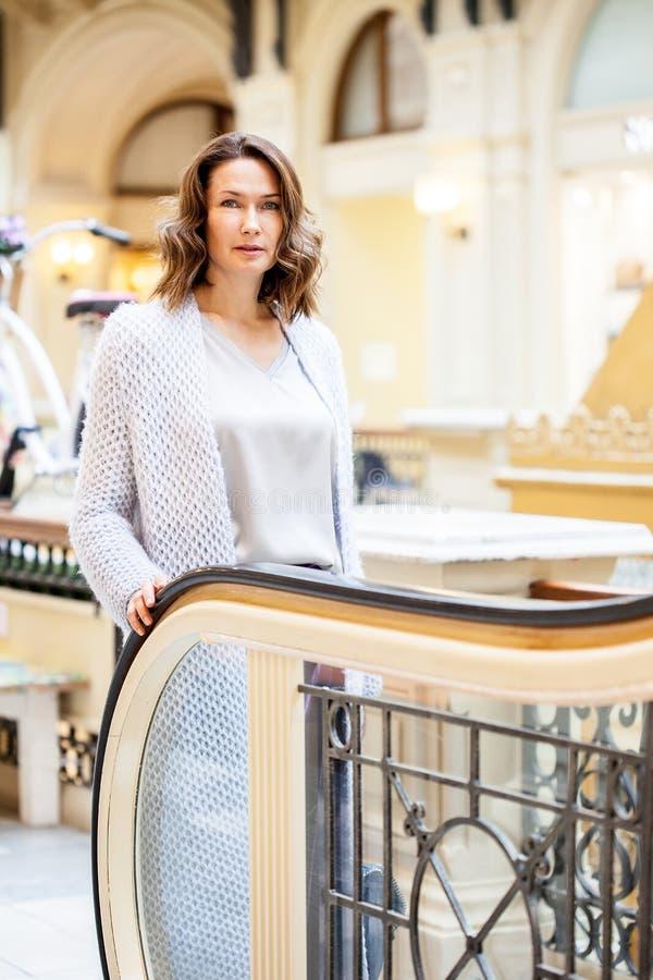Женщина в свете связала пальто около эскалатора стоковые фотографии rf