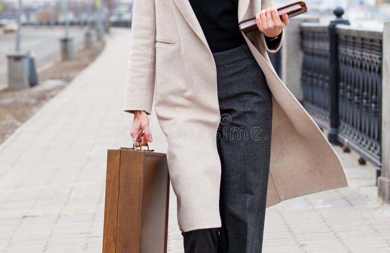 Женщина в светлом пальто, с деревянным случаем и книгой в его руках outdoors стоковые изображения