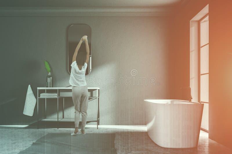 Женщина в серой ванной комнате просторной квартиры, взгляде со стороны ушата раковины иллюстрация вектора