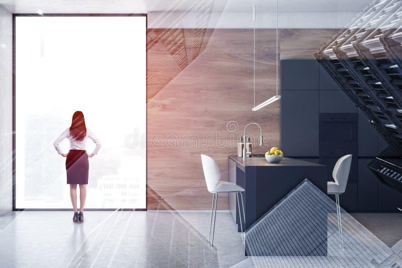 Женщина в серой и деревянной кухне с островом стоковая фотография rf