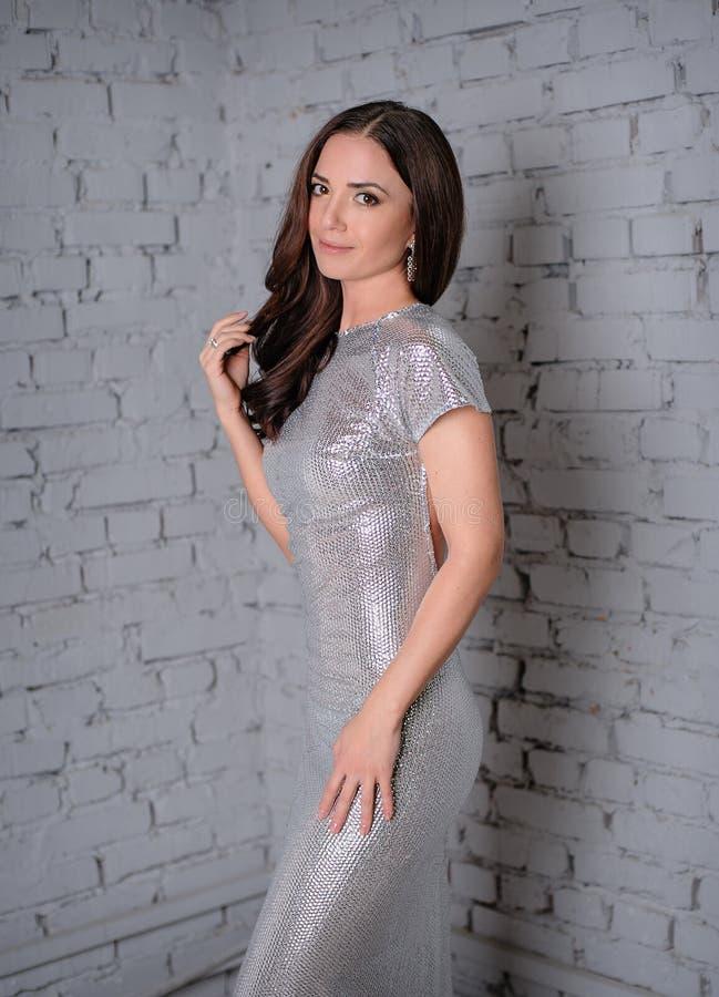 Женщина в сером платье на предпосылке кирпичной стены стоковое изображение