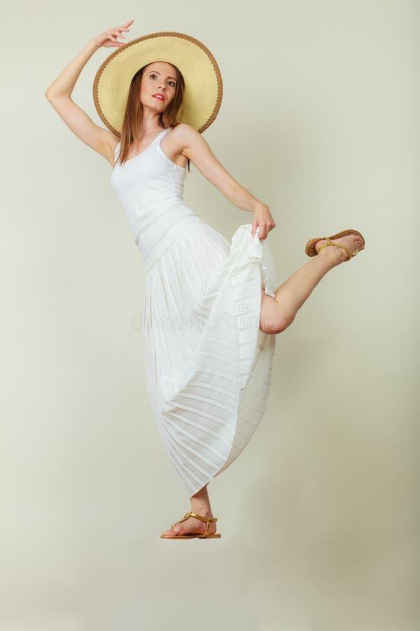 Женщина в скакать платья шляпы лета соломы белый стоковая фотография rf