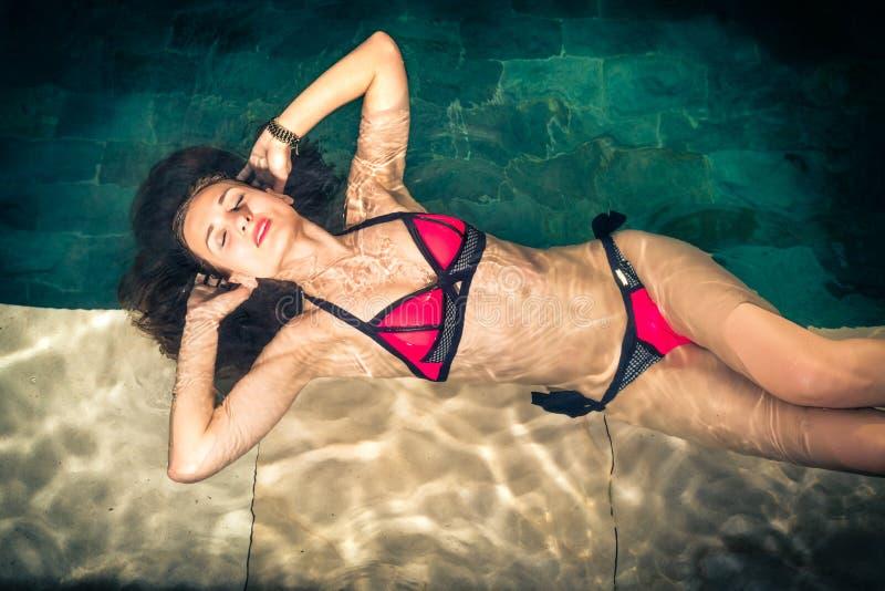 Женщина в склонности каникул на крае бассейна стоковое фото