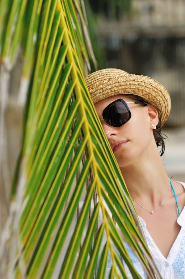Женщина в солнечных очках приближает к пальме стоковая фотография rf