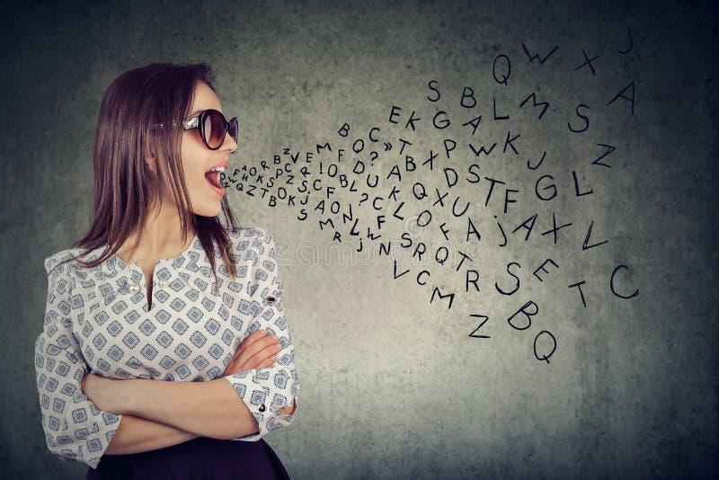 Женщина в солнечных очках разговаривая с алфавитом помечает буквами приходить из ее рта стоковые изображения