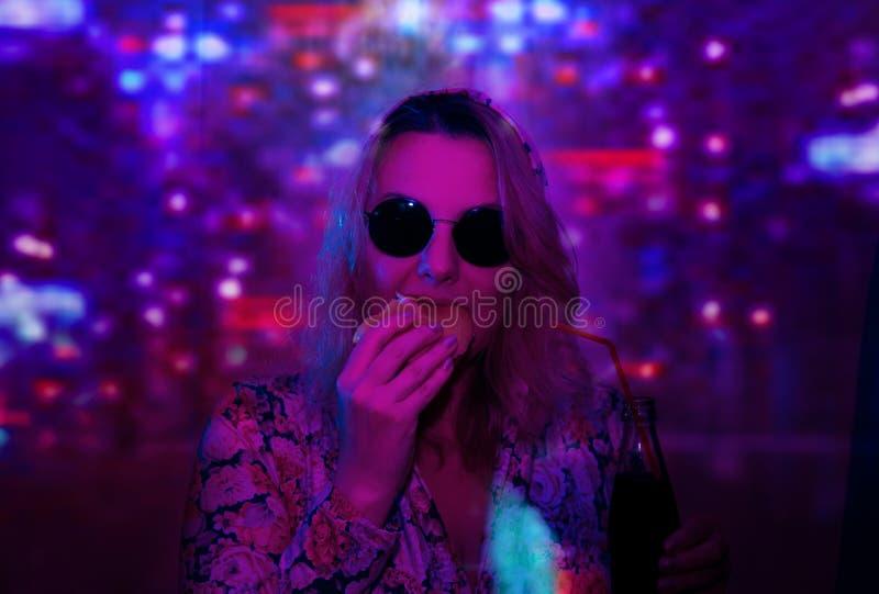 Женщина в солнечных очках с отражением неонового света девушки стоковая фотография