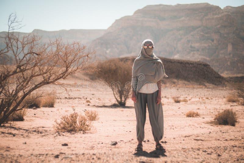 Женщина в солнечных очках и шарфе в пустыне стоковое изображение rf