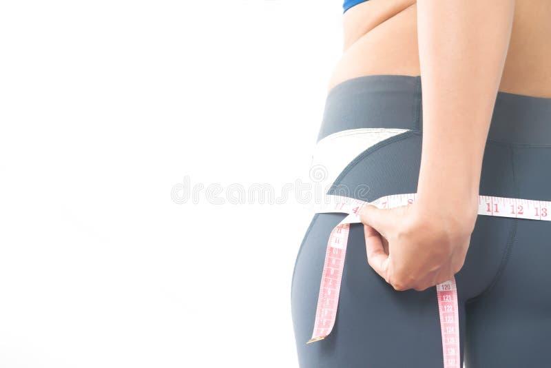 Женщина в спорте задыхается держащ измеряя ленту на бедре, здоровом и стоковая фотография