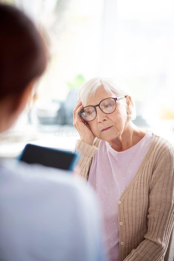 Женщина в стаканах в отставке с сильной головной болью стоковые изображения rf