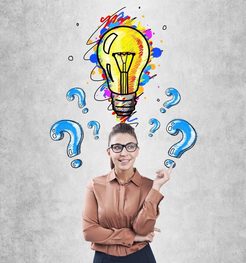 Женщина в стеклах показывая электрическую лампочку, вопросы стоковые фото