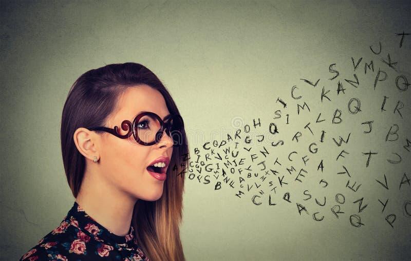 Женщина в стеклах разговаривая с алфавитом помечает буквами приходить из ее рта стоковое фото rf