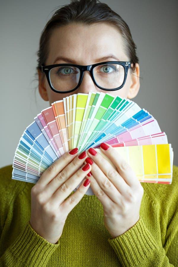 Женщина в стеклах смотря к цветовой палитре стоковые изображения rf